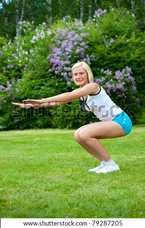 An active beautiful caucasian woman doing sit-ups in the park
