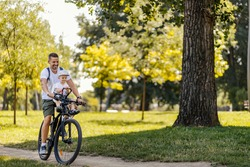 An active family day in nature. A father and son ride a bike through the woods on a sunny summer day. A cute boy is sitting in a bicycle basket while he rides a bicycle. They enjoy the ride