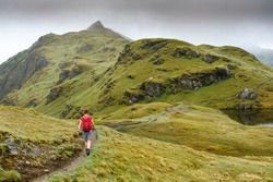 An active female hiker walking down from Meall nan Tarmachan towards Meall Garbh near Loch Tay in the Scottish Highlands, UK hiking.