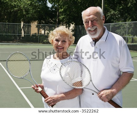 An active, happy senior couple on the tennis courts.