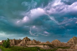 An active lightning storm over the mountains of Badlands National Park in South Dakota lights up the sky.