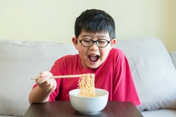 An adorable and starving little Asian kid is eating the fresh cooked noodle with the wooden chopsticks.The hungry boy is opening his mouth widely and ready to have the instant meal from a white bowl.