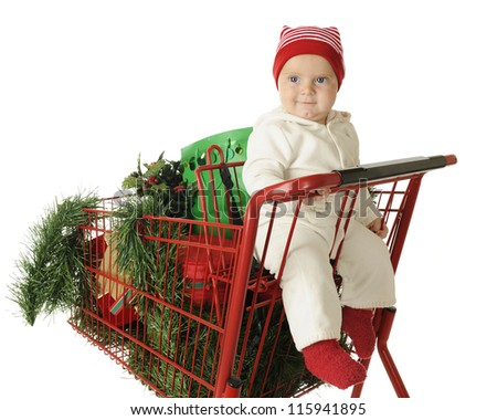 An adorable baby boy happily sitting in the child's seat of a red shopping cart filled with Christmas goodies.  On a white background.
