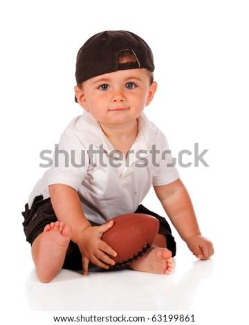 An adorable baby boy in a backwards cap holding his football.  Isolated on white.