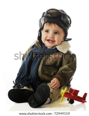An adorable baby boy in an old-fashioned pilot's outfit with a toy wooden airplane.  Isolated on white.