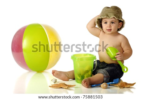 An adorable baby boy in capri and a hat happily sitting among beach toys and sea shells.  Isolated on white.