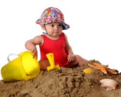 An adorable baby girl in a bathing suit and sunhat playing in the sand.  Isolated on white.