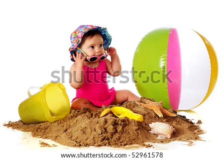 An adorable baby girl trying on sunglasses as she plays in a pile of sand with beach toys and shells.  Isolated on white.