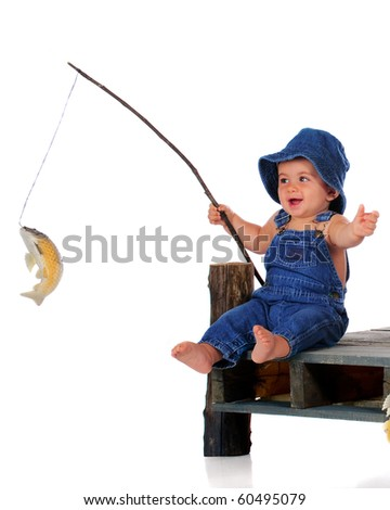 An adorable baby in overalls happily pulls up a fish on his line.  Isolated on white.