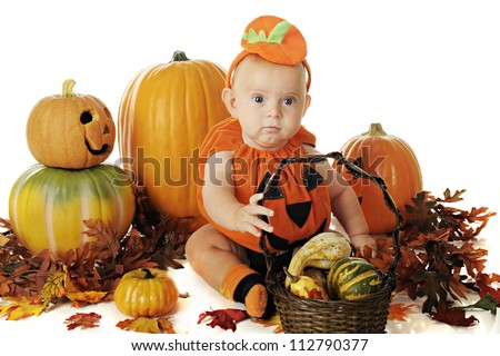 An adorable baby wearing a pumpkin costume while sitting among other pumpkins and autumn leaves.  he holds a basket of gourds.  On a white background.