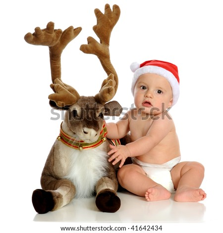An adorable baby wearing Santa's hat posing with a plush reindeer.