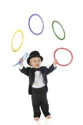 An adorable, barefoot toddler juggling colorful rings in his tuxedo and top hat.  Motion blur on the rings.  On a white background.