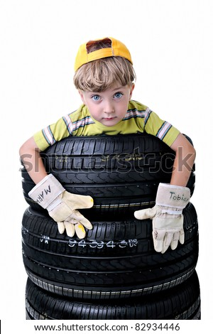 An adorable boy with gloves lifting a tire. Isolated on white.