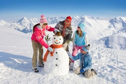 An adorable family having fun while building and decorating a snowman together in front of a magnificent range of snow mountains