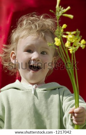 An adorable laughing 2 year old with flowers and a look of surprise and awe at her wonderful find.