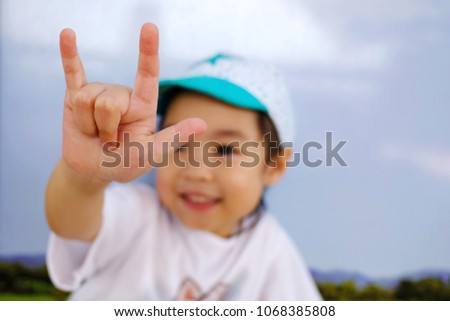 "An adorable little asian girl show her hand, the sign hand language ""I love you"". Blured if her face, focus at her finger."