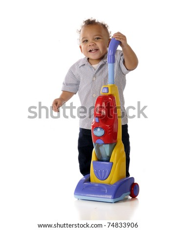 An adorable mixed race toddler showing off his toy upright vacuum cleaner.  Isolated on white.