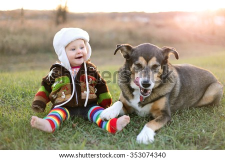 An adorable 8 month old baby girl is bundled up in a sweater and wearing a winter earflap hat looking lovingly at her pet German Shepherd dog as they sit and laugh outside on a cold fall day.