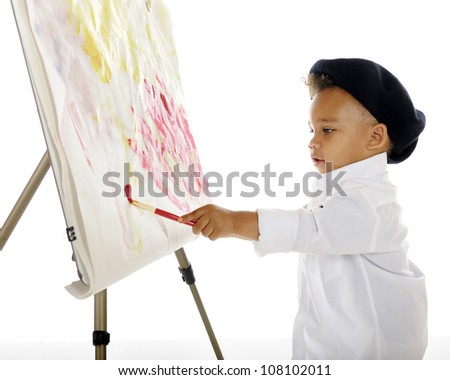 An adorable preschool artist painting on an easel while wearing a white smock and black French beret.  On a white background.