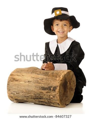 An adorable preschool boy dressed as a pilgrim, happily kneeling to pray before an old log.  Isolated on white.