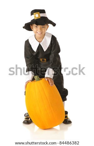 An adorable preschool boy wearing Pilgrim clothes happily attempting to lift a large pumpkin.  Isolated on white.