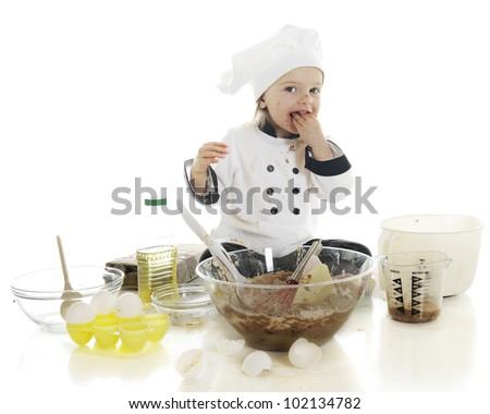 "An adorable preschool ""chef"" tasting a fistful of the chocolate cake batter that she's been making.  On a white background."