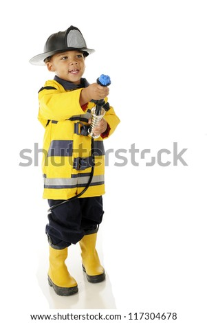 "An adorable preschool in full ""Fire Chief"" gear aiming his hose toward a (pretend) fire.  On a white background."
