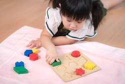 An adorable preschool little girl 2-3 years in Montessori classroom engaged sensory wooden shape and color blocks. Educational toys, Cognitive skills, Child development, Learn through play concept.