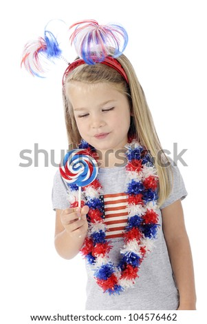 An adorable preschooler dressed to celebrate Independence Day, looking longingly at the red, white and blue swirled lollipop she holds.  On a white background.