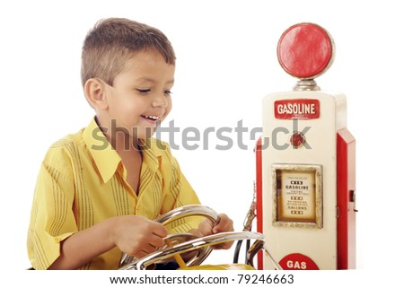 An adorable preschooler happily driving his car by an old-time gas pump.  Isolated on white.