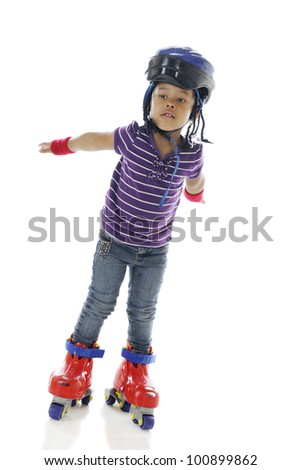 An adorable preschooler holding her arms out as if in flight as she gains confidence on her plastic roller blades.  On a white background.