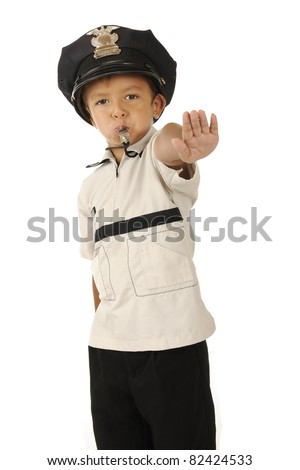 An adorable preschooler in a policeman's hat blowing his whistle and holding out his hand demanding traffic to stop.  Isolated.