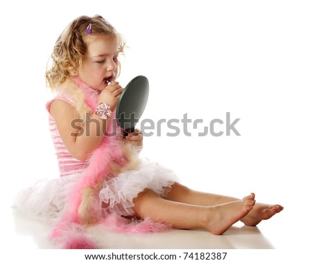 An adorable preschooler in boas and a petticoat, applying her mommy's makeup onto herself.