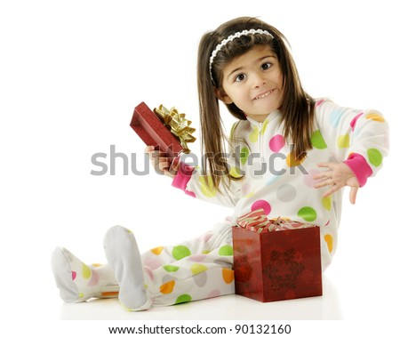 An adorable preschooler in her pajamas excitedly opening a gift.  On a white background.