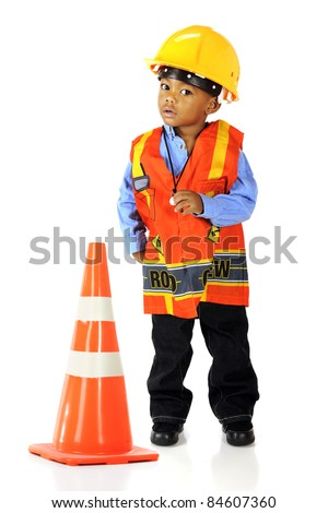 An adorable preschooler in road crewman safety gear by a an orange traffic cone.  Isolated on white.