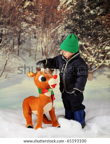 An adorable preschooler in winter wear dumping snow on a large, toy reindeer.