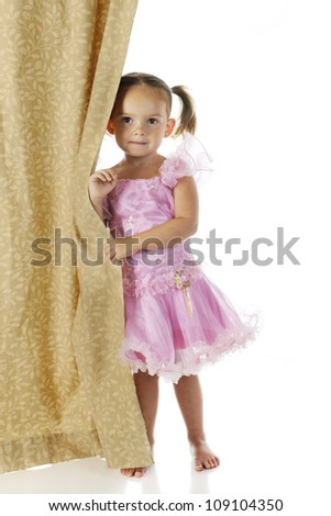 An adorable preschooler peeking from behind a curtain in her pink princess dress.  On a white background.