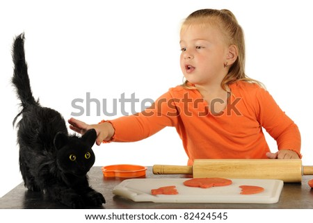 An adorable preschooler playing with modeling dough cautiously reaching out to touch a scary black cat.