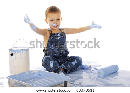 An adorable preschooler sitting among wall-painting supplies.  He's happily clapping his paint-soaked hands.  Isolated on white.
