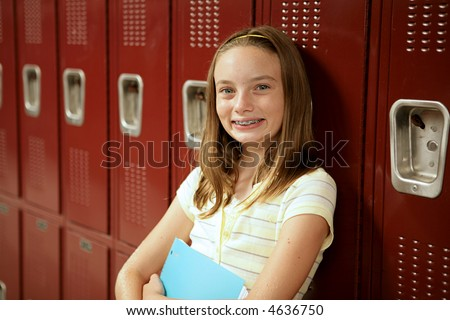 An adorable teen girl with braces and freckles standing in front of her locker.