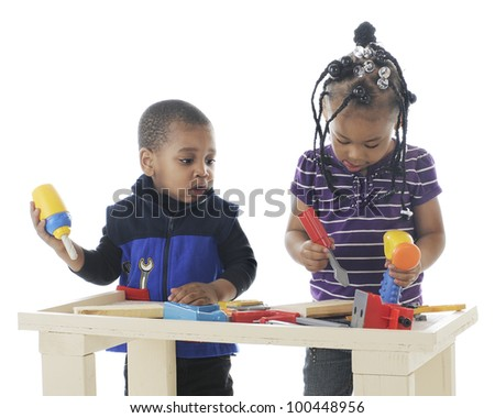 An adorable toddler boy watching what is preschool sister is doing with the toy tools on a workbench.  On a white background.