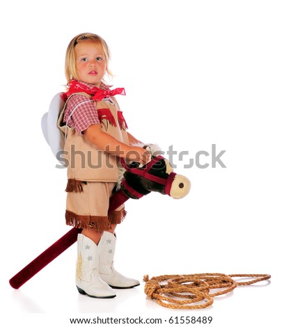 An adorable two-year-old cowgirl riding a stick-horse.  Isolated on white.