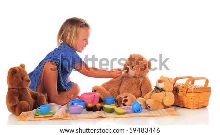 An adorable two-year-old happily feeding her Teddy bear while hosing a picnic for 3.  Isolated on white.