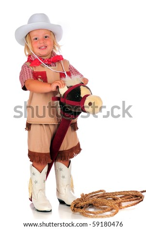 An adorable 2-year-old playing cowgirl while riding a stick horse.  Isolated on white.