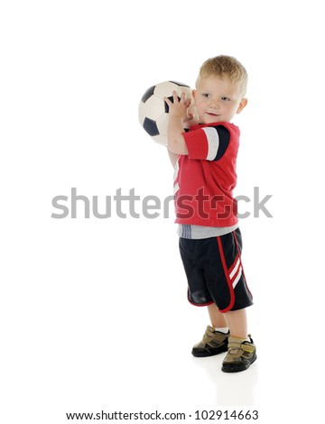 An adorable 2-year-old preparing to toss his soccer ball.  On a white background.