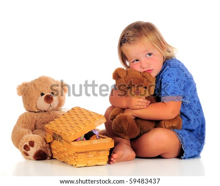 An adorable 2-year-old squeezing her Teddy bear with another bear and small, opened picnic basket nearby.  Isolated on white.