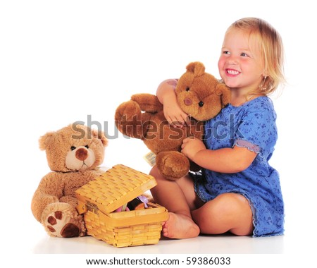 An adorable 2 year-old with teddy bears preparing to have a picnic with them.  Isolated on white.