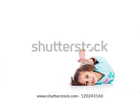 An adorable young girl laying down playfully