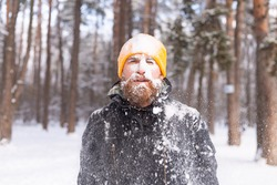 An adult brutal man with a beard in a winter forest all face in the snow, frozen, unhappy with the cold