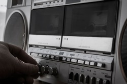 An adult Caucasian male hand increases the volume on a retro stereo cassette recorder. Vintage audio equipment of the last century. Selective focus.